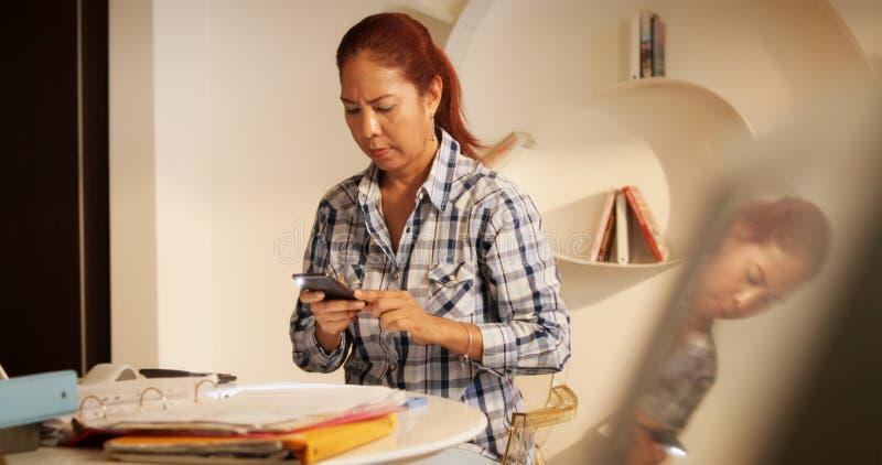 Document d'impôts de balayage de femme et photo de prise avec Smartphone photographie stock
