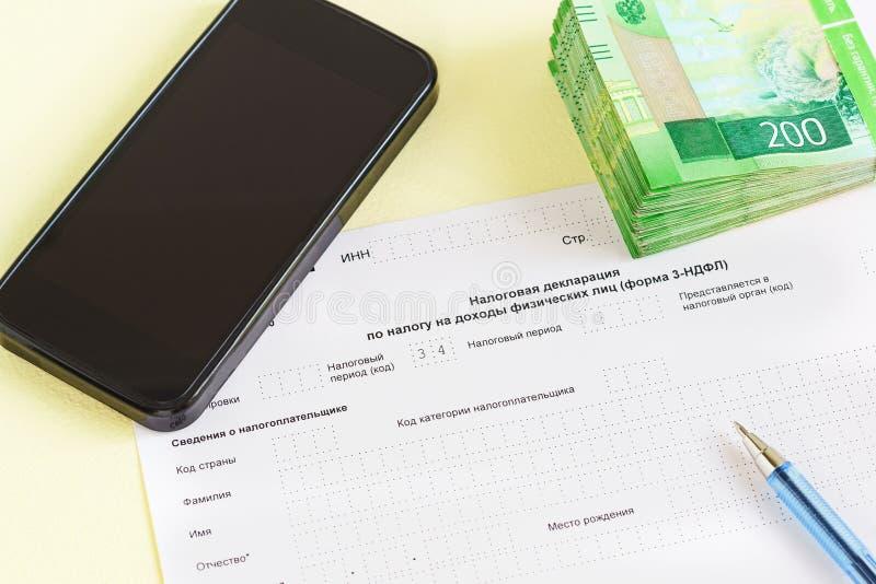 Document dans la langue russe : De la déclaration d'impôts sur l'impôt aux revenus du plan rapproché, du stylo, du smartphone et  image libre de droits