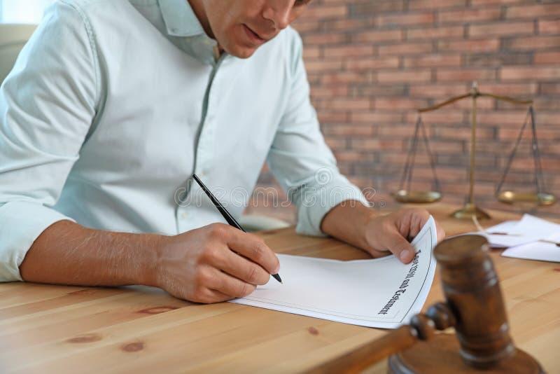Document de signature de notaire masculin à la table dans le bureau, photographie stock libre de droits