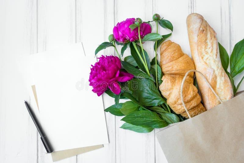 Document het winkelen de zak met vers brood, de croissants, de pioenbloemen en het winkelen de lijstvlakte leggen, hoogste mening royalty-vrije stock afbeeldingen