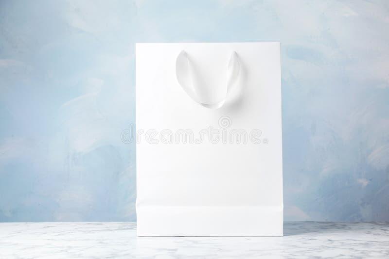 Document het winkelen zak met linthandvatten op lijst tegen kleurenachtergrond stock foto's