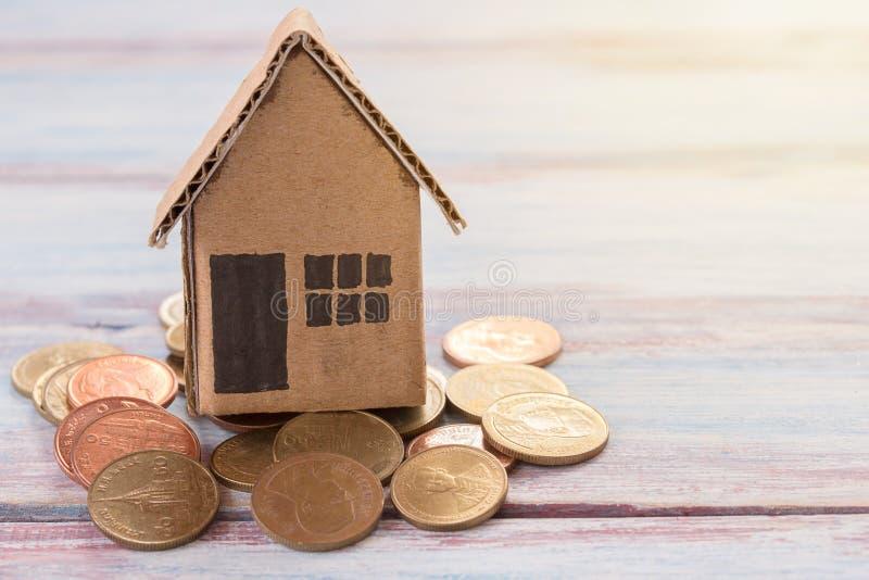 Document huisstuk speelgoed of kartonhuis en muntstukken op houten lijst stock foto