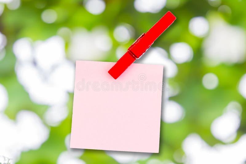 Document kleur en houten klemnota over Groene bokeh stock fotografie
