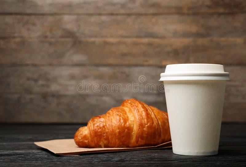 Document kop met koffie en croissant op houten lijst stock foto