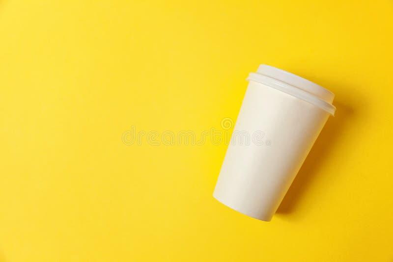 Document kop van koffie op gele achtergrond stock afbeelding