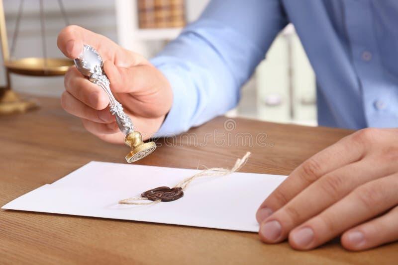 Document masculin de cachetage de notaire à la table dans le bureau, image stock