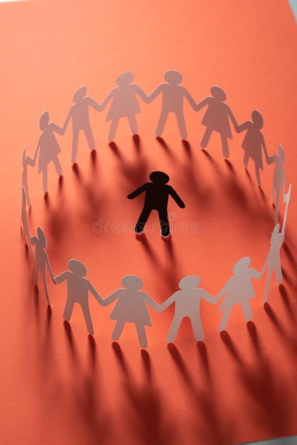 Document menselijk die cijfer door cirkel van document mensen wordt omringd die handen op rode oppervlakte houden Bulling, scheid royalty-vrije stock fotografie