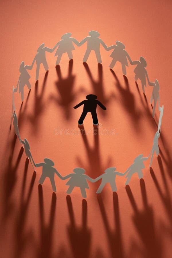 Document menselijk die cijfer door cirkel van document mensen wordt omringd die handen op rode oppervlakte houden Bulling, scheid royalty-vrije stock afbeeldingen