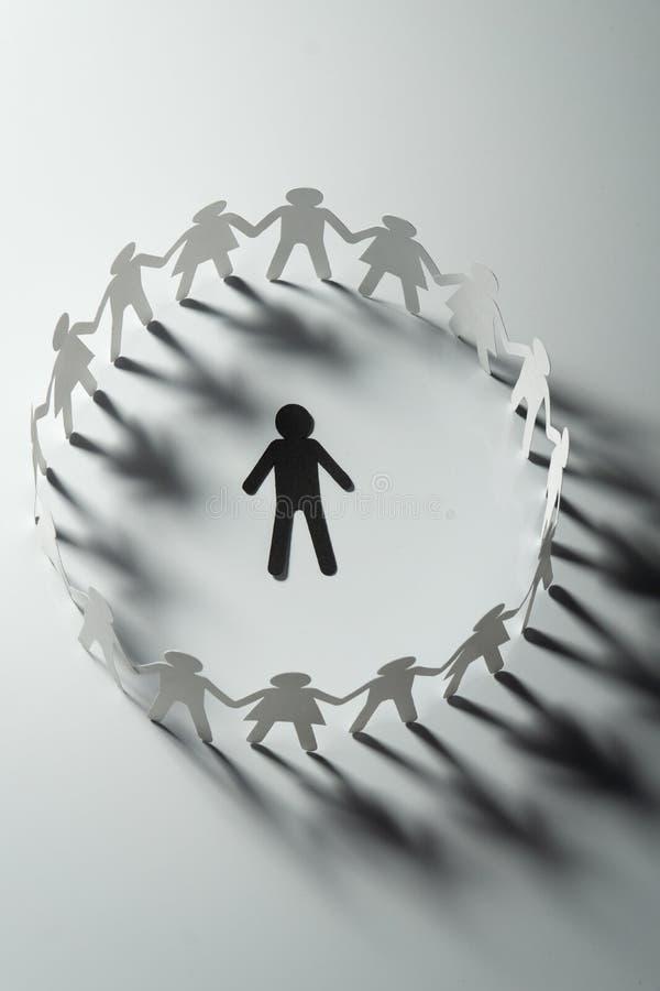 Document menselijk die cijfer door cirkel van document mensen wordt omringd die handen op witte oppervlakte houden Bulling, schei stock foto