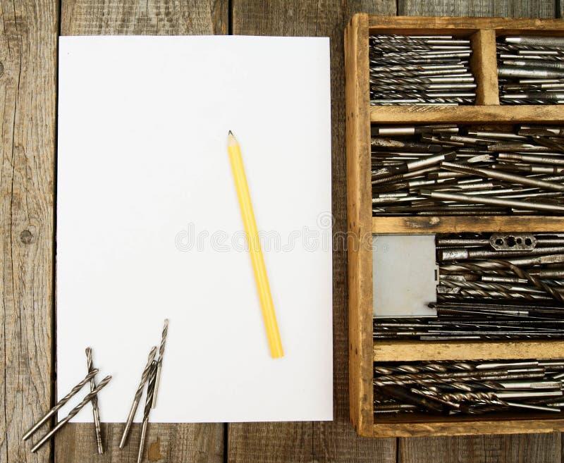 Document met potlood en vakje, boren op houten royalty-vrije stock fotografie