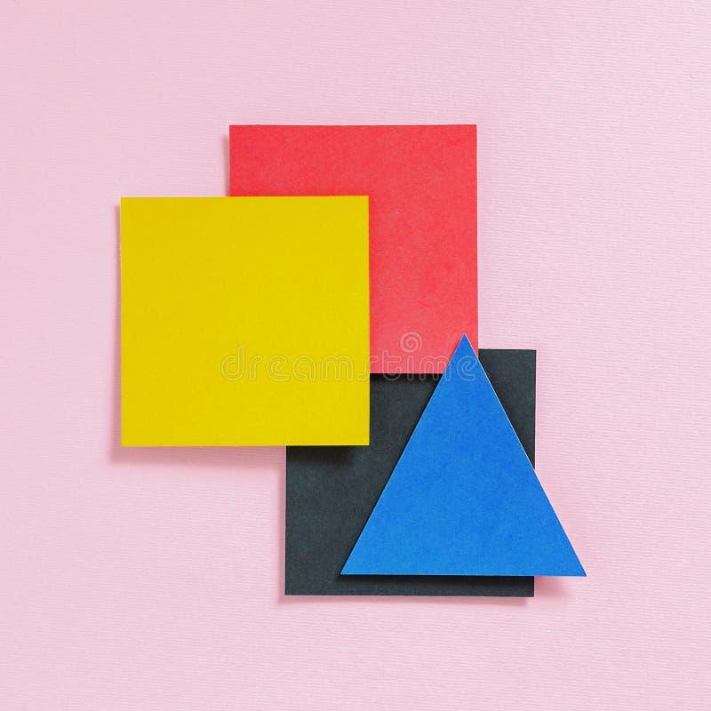 Document multicolored vierkanten en een driehoek op een roze achtergrond stock foto