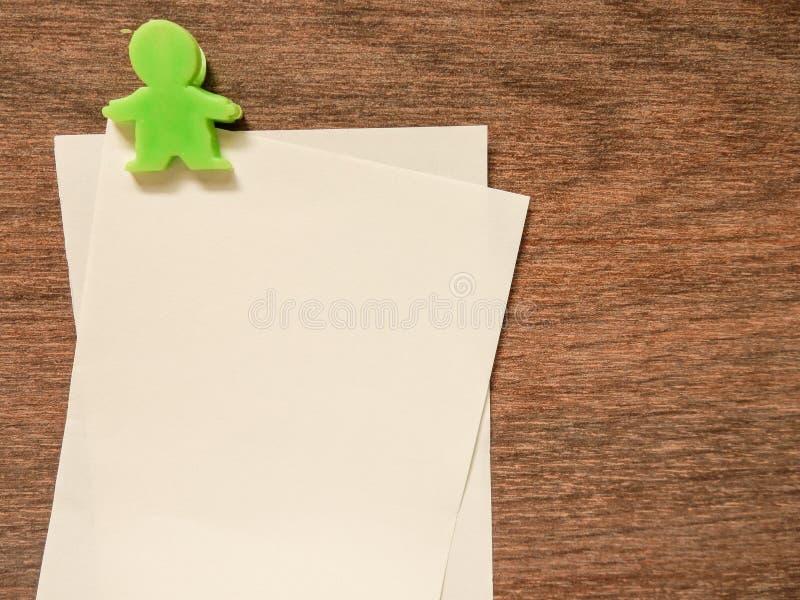 Document nota met groene klem op houten achtergrond stock foto's