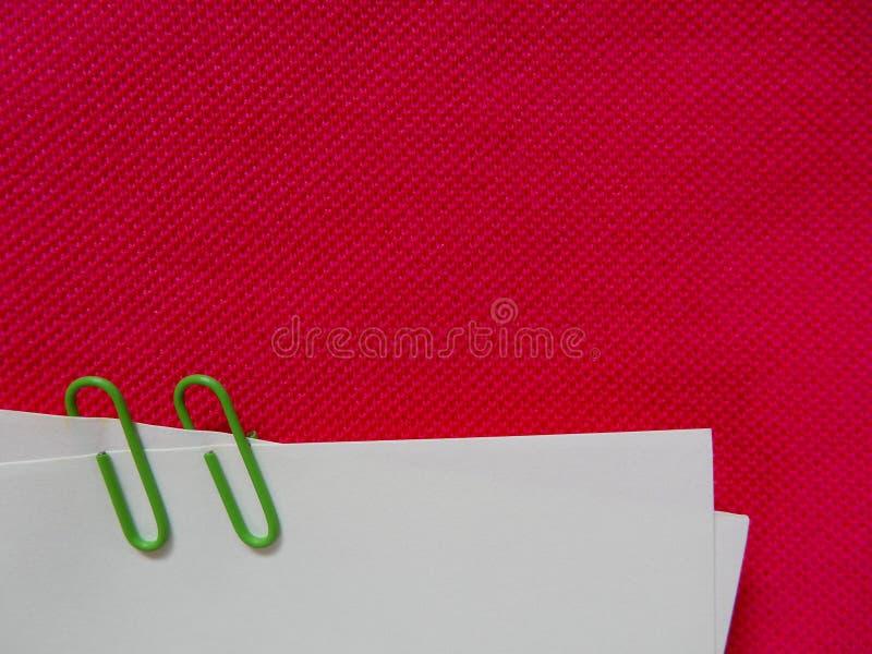 Document nota met groene klem op roze stof royalty-vrije stock afbeelding
