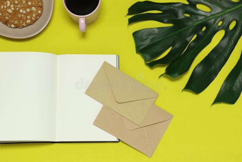 Document nota's, ambachtenveloppen, groen blad, voedsel over de gele lijst stock foto