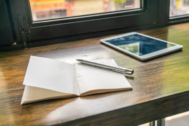 Document notitieboekje en tablet op houten lijst naast venster stock afbeelding