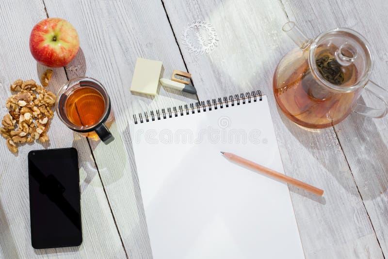 Document notitieboekje, potlood, kop thee, appel, cellphone en okkernoten op houten lijst stock afbeeldingen