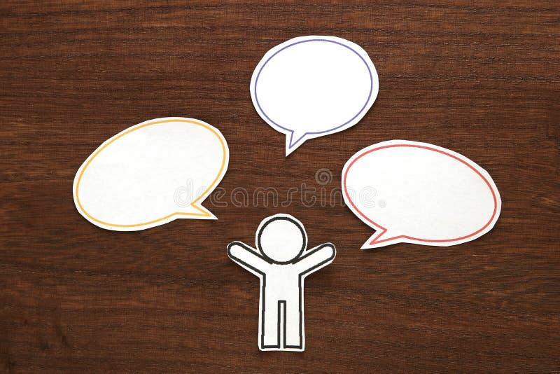 Document persoon met de kleurrijke lege bellen van de dialoogtoespraak op bruin hout Communicatie concept stock foto's