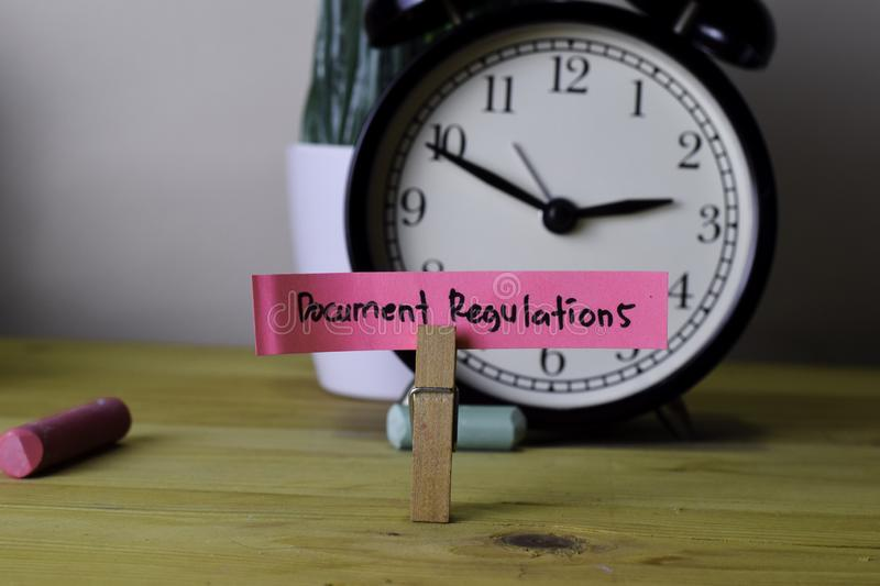Document Regulations. Handwriting on sticky notes in clothes pegs on wooden office desk royalty free stock photo