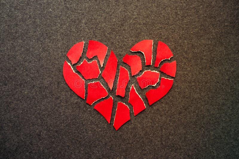 Document rood gebroken hart op dark gevoelde achtergrond Mozaïekdocument hea stock foto's