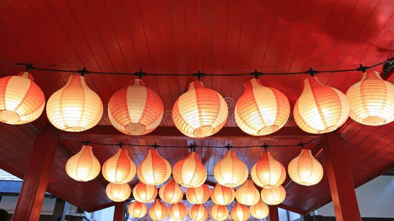 Document rood-witte Aziatische Japanse lantaarns in rij het gloeien stock afbeeldingen