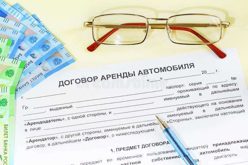 Document in Russian: Car rental Agreement, glasses, money and a pen on the table. Office work stock photos