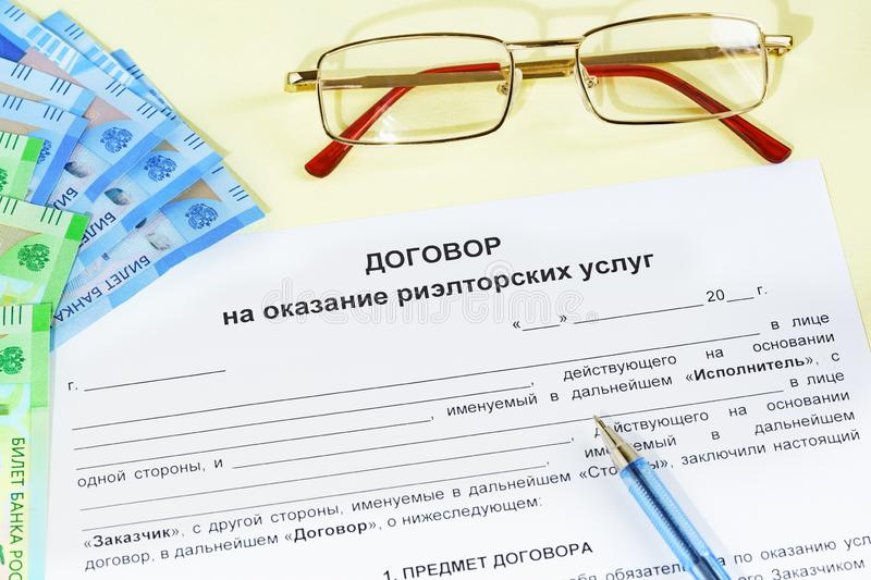 Document in Russian Contract for the provision of real estate services, glasses, money and a pen on the table royalty free stock photo