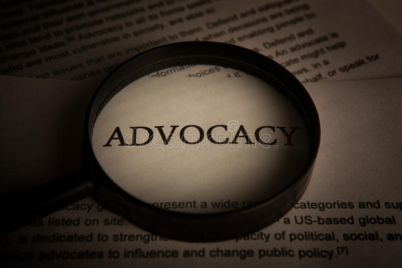 Document with the title of advocacy under a magnifying glass. Closeup royalty free stock photo