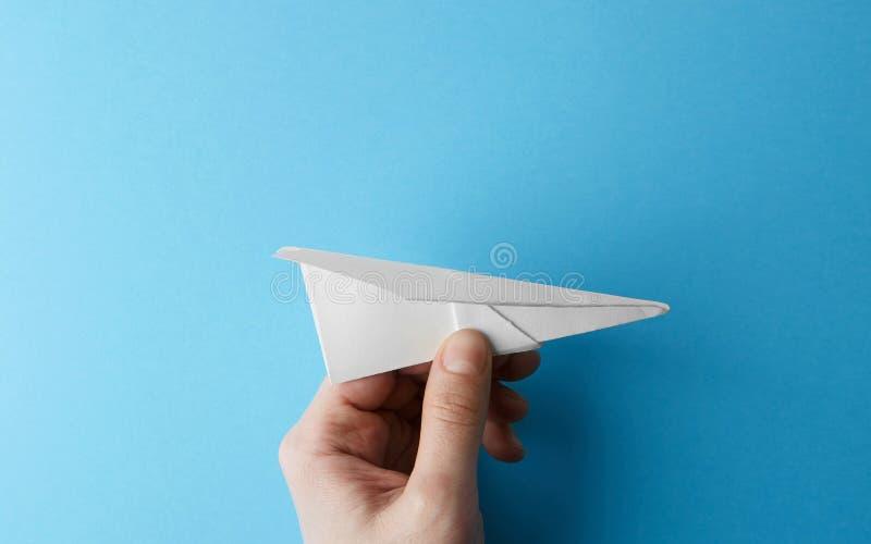 Document vliegtuig op blauwe holding als achtergrond in mannelijke hand Het concept van de reis en van het toerisme horizontaal royalty-vrije stock foto