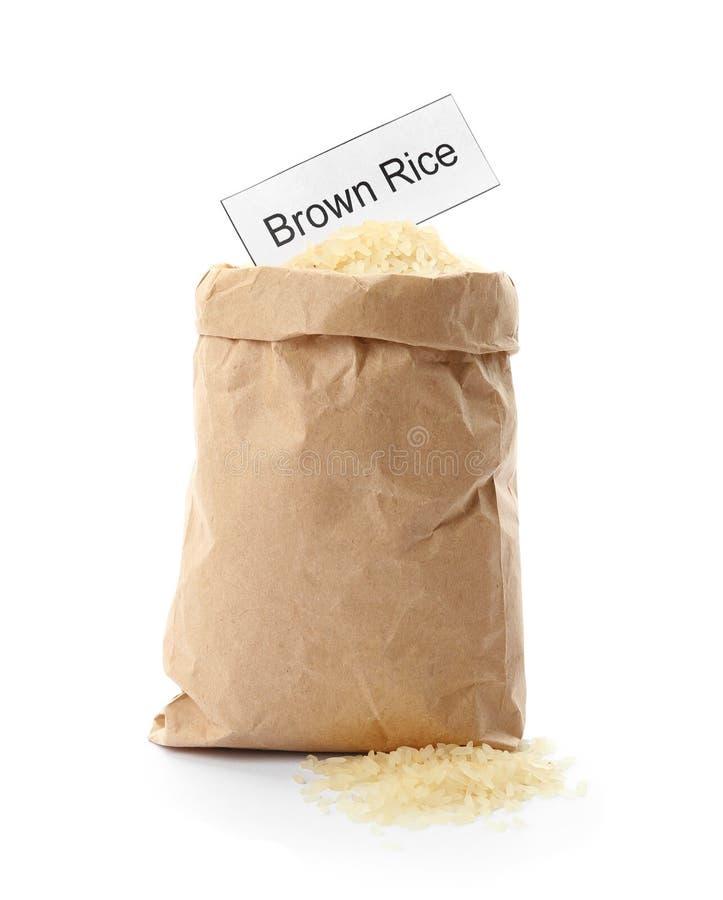 Document zak met ongekookte ongepelde rijst en kaart op witte achtergrond stock fotografie
