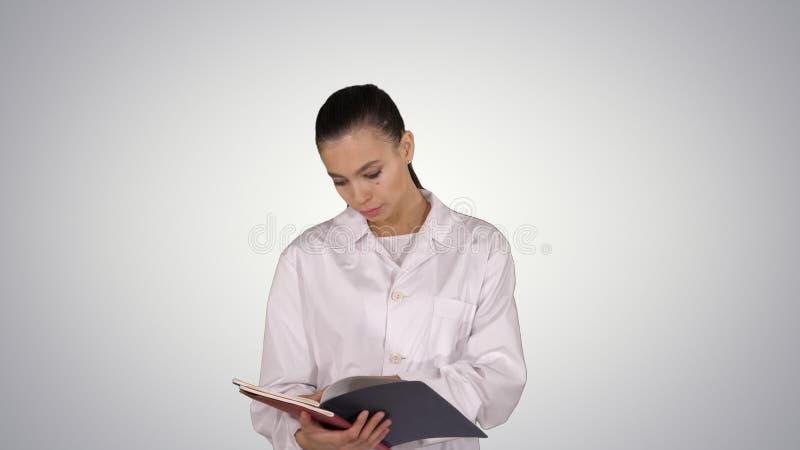 Documentaci?n joven de la lectura de la mujer del doctor mientras que camina en fondo de la pendiente imagen de archivo