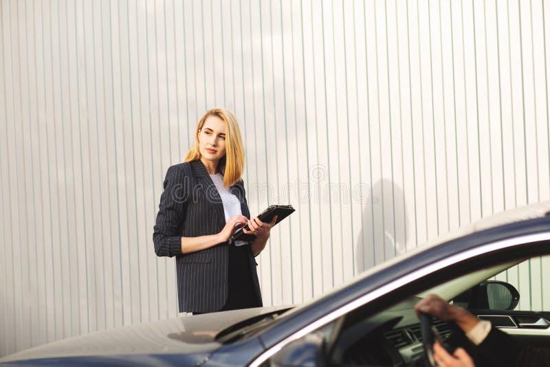 Documenten die door de vrouwenwerknemer, dichtbij de zwarte auto controleren stock afbeelding