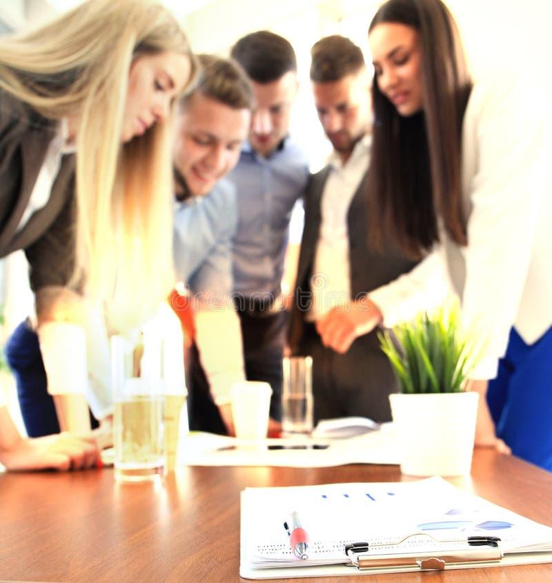 Documenten met grafiek en grafiek en pen op achtergrond van vijf werknemers het werken stock afbeelding