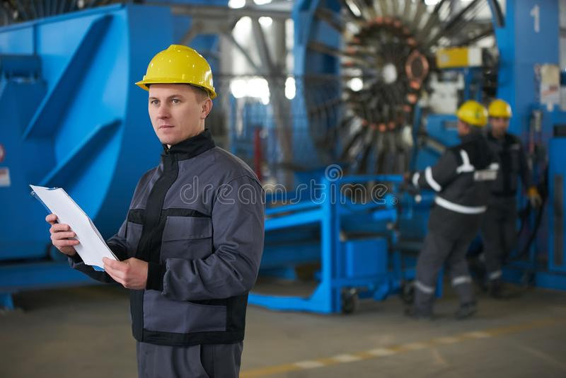 Documenti cartacei della lettura del lavoratore mentre stando alla fabbrica immagini stock