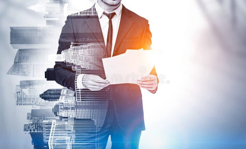 Documenti della lettura dell'uomo d'affari in città, falsa su immagine stock