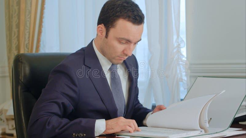 Documenti della lettura dell'uomo d'affari e parlare sul telefono della linea terrestre fotografia stock libera da diritti
