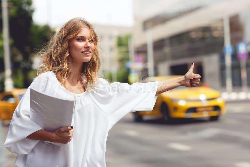 Documenti della tenuta della donna di affari e fermate del taxi fotografia stock