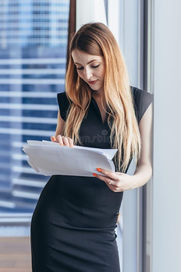 Documenti della tenuta della donna, guardando attraverso le carte, studianti il rapporto che sta finestra vicina con la vista sui immagini stock libere da diritti