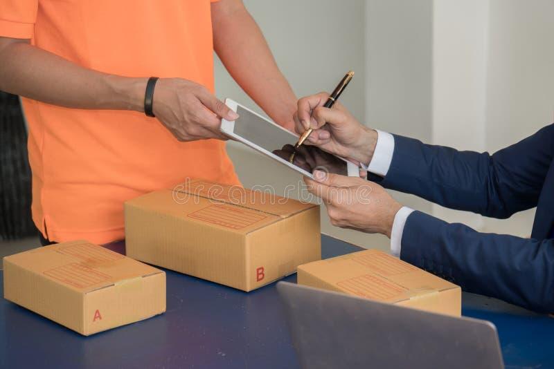 Documenti di firma dell'uomo di affari dopo la ricezione delle merci dal deliverer fotografia stock libera da diritti