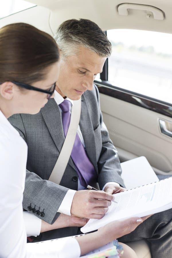 Documenti di firma dell'uomo d'affari mentre sedendosi dal collega in automobile fotografie stock libere da diritti