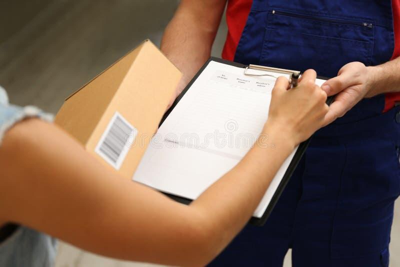 Documenti di firma della giovane donna dopo la ricezione del pacchetto fotografie stock libere da diritti