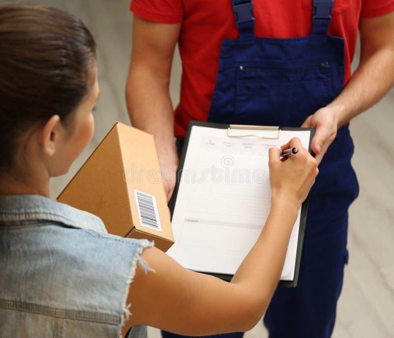 Documenti di firma della giovane donna dopo la ricezione del pacchetto fotografia stock
