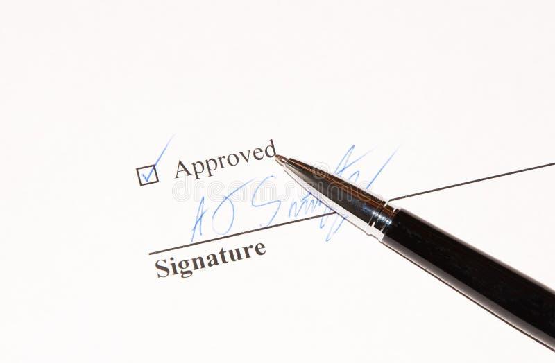 Documenti la firma di approvazione in inchiostro blu su una penna nera fotografie stock
