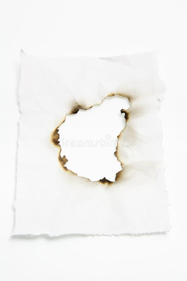 Documento con il foro bruciato fotografie stock