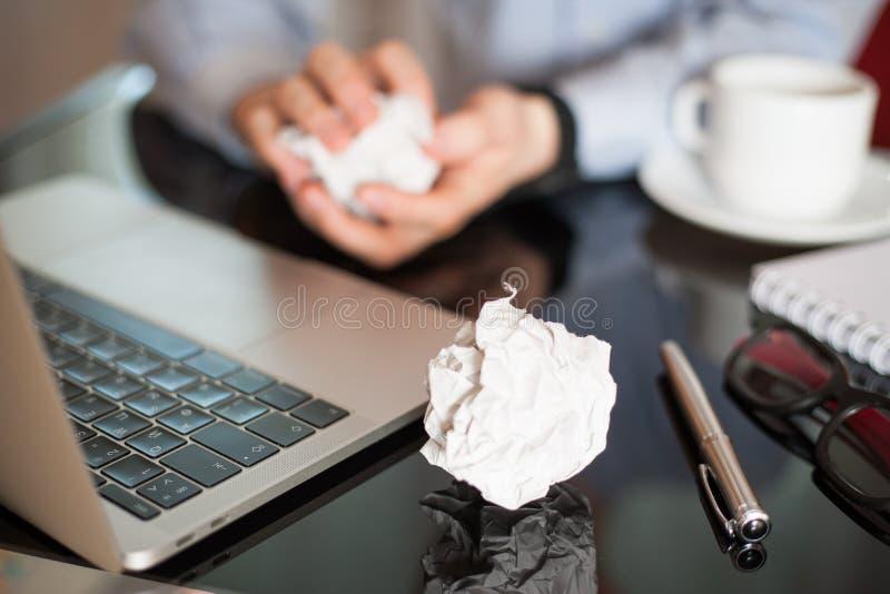 Documento de arrugamiento del hombre de negocios sobre su lugar de trabajo Lugar de trabajo de la oficina con las bolas de papel  imagen de archivo