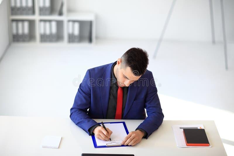 Documento de assinatura do homem de negócios que senta-se em sua mesa no escritório fotos de stock