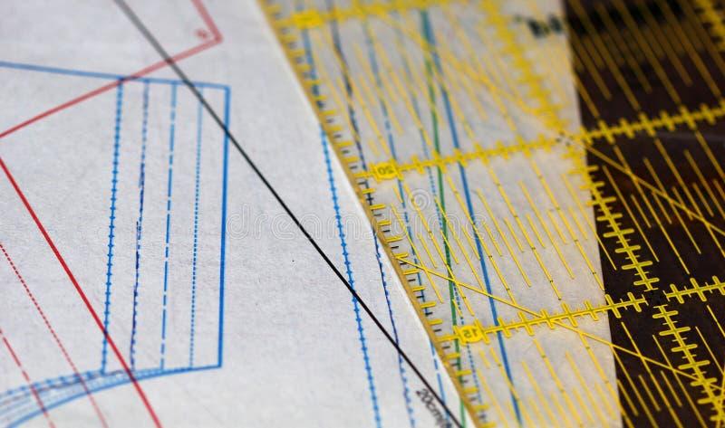 Documento de costura del dibujo, de la regla y de trazo sobre la tabla imagen de archivo