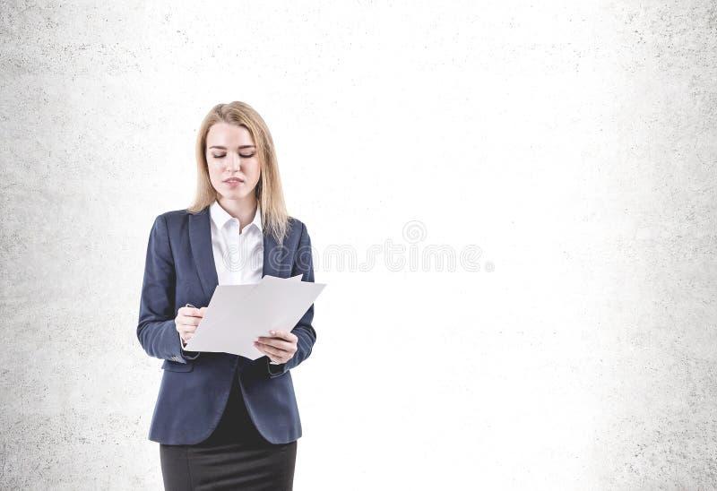 Documento de firma serio de la mujer joven, concreto fotos de archivo libres de regalías