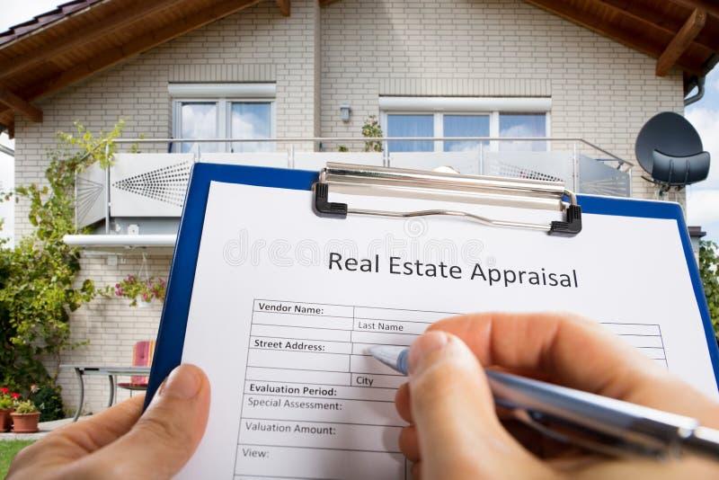 Documento de la valoración de Person Hand Filling Real Estate foto de archivo