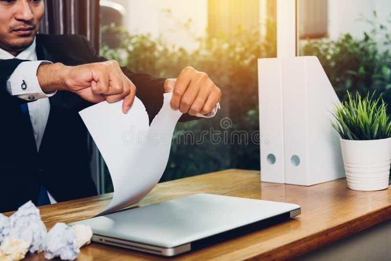Documento de papel de rasgado de fractura enojado del hombre de negocios foto de archivo