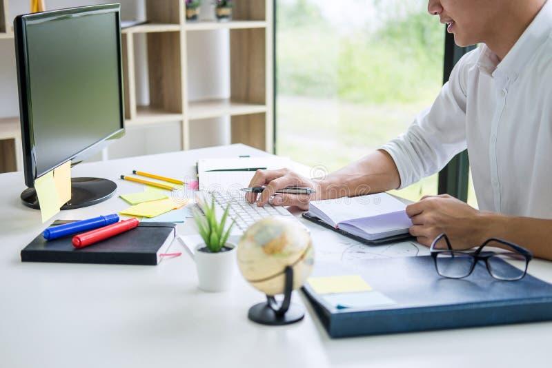 Documento de trabajo del plan empresarial de la escritura del hombre de negocios y dise?ador gr?fico con el ordenador en oficina imagen de archivo